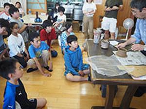 陶芸体験の説明を聞いています。
